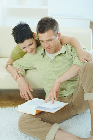 Young couple resting at home couch, reading book, embracing. Stock Photo - 5183055