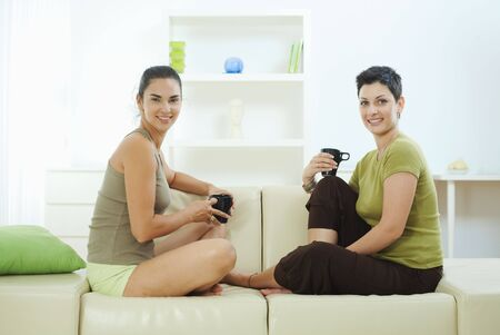 Two women sitting together on couch at home, drining coffee, smiling. photo