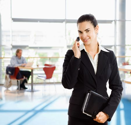 Young businesswoman wearing black suit, holding personal organizer talking on mobile phone in office building lobby. photo