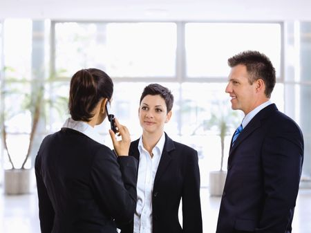 Young businesspeople talking in office lobby, using mobile phone. photo