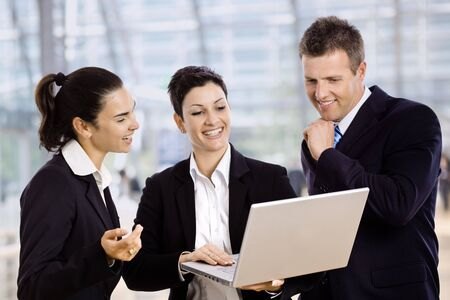 Three young businesspeople standing in lobby, looking at laptop computer screen, smiling. Stock Photo - 5182992