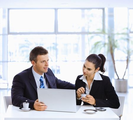 Businessman and businesswoman having a meeting in office lobby, drinking coffee. Stock Photo