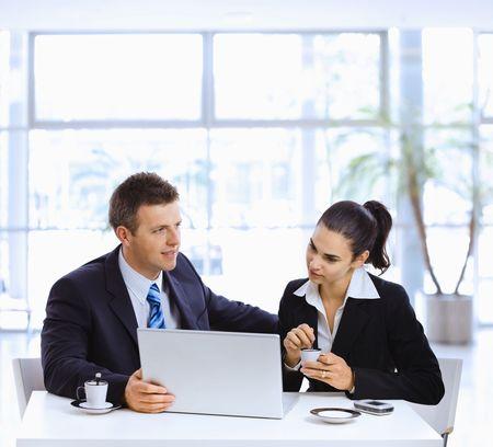 deux personnes qui parlent: Homme d'affaires et femme d'affaires ayant une r�union de bureau de lobby, de boire du caf�. Banque d'images