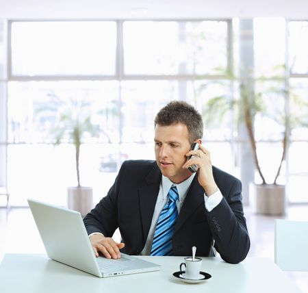 calling on phone: Businessman sitting at table in office hall, talking on mobile phone and using laptop computer. Stock Photo