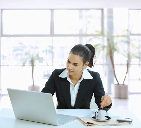 Businesswoman sitting at table in office lobby, stirring coffee and using laptop computer. Stock Photo - 5183019