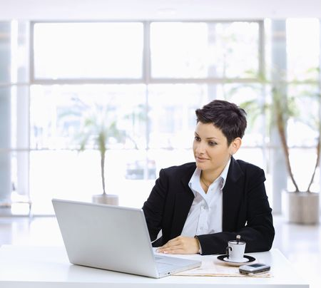 Businesswoman sitting at table in office lobby, using laptop computer, looking at screen. photo