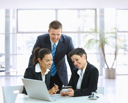 Young businesspeople talking in office lobby, looking at smart mobile phone, smiling. Stock Photo