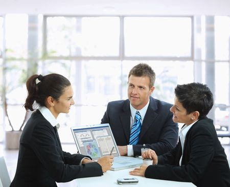 mujeres sentadas: J�venes empresarios con una reuni�n de negocios en la mesa de caf� en el vest�bulo de la oficina, con ordenador port�til. Foto de archivo