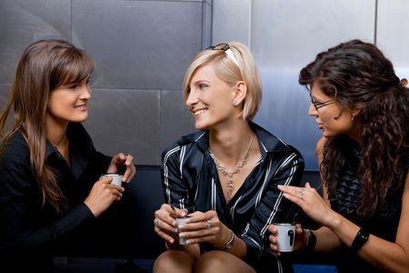 Group of young businesswomen sitting on couch in office lobby, drinking coffee, talking. photo