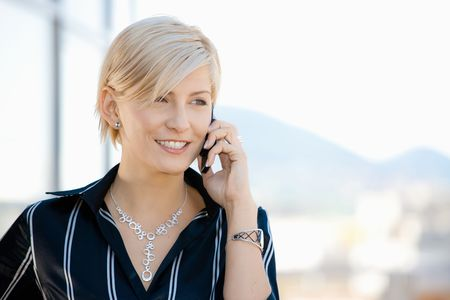 Young businesswoman talking on mobile phone, outside office building. Stock Photo - 5183011