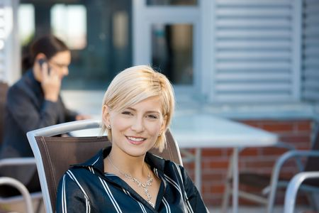 Portrait of attractive young businesswoman sitting in chair, smiling. photo