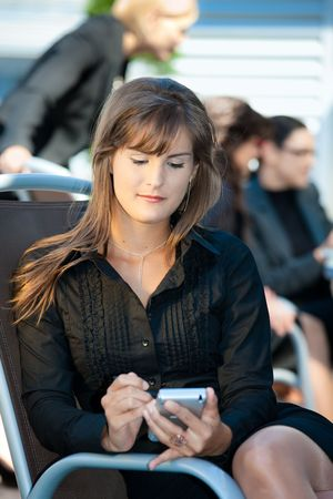 officetower: Young businesswoman sitting in chair, using smart phone.