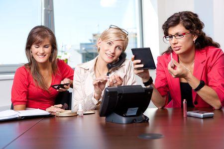 open collar: Young ausinesswomen adjusting makeup in meeting room.
