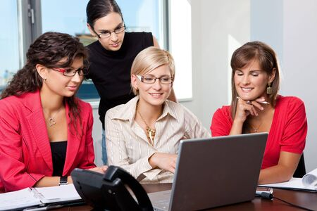 Team of young businesswomen sitting at table in meeting room, using laptop computer, smiling. photo