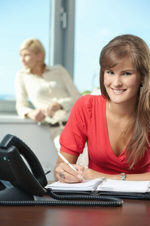 Young businesswoman sitting at desk in office, writing notes into personal organizer, smiling. photo