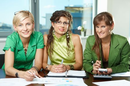 Young  businesswomen sitting at table in meeting room, discussing charts on table, looking at camera, smiling. photo