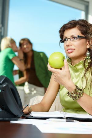 Young businesswoman sitting at office desk, holding green apple, smiling photo