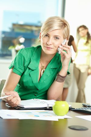 Young businesswoman sitting at desk in office, talking on mobile, smiling. Stock Photo - 5183040