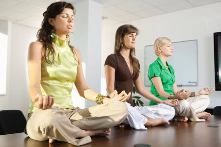 exercise room: Young businesswomen sitting in lotus position on meeting room table. Stock Photo