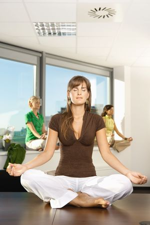 Young businesswomen sitting in yoga position in office. Stock Photo