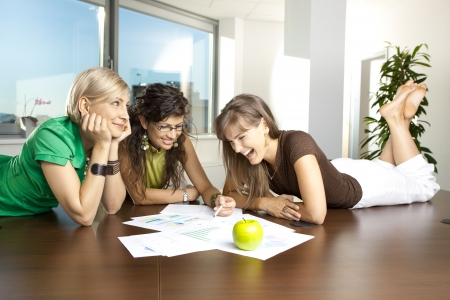 Casual businesswomen lying on table in meeting room, discussing business charts on paper. photo