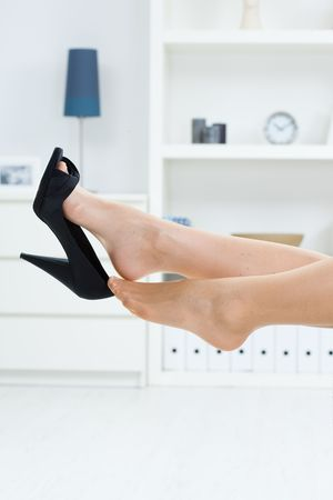 high heel shoes: Woman legs in stockings, taking off high heel shoes. Stock Photo