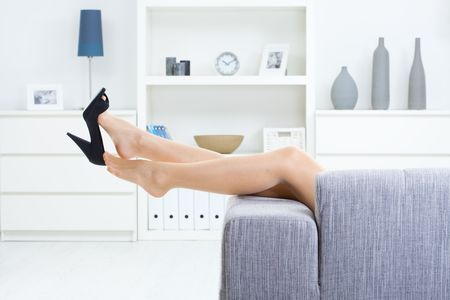 attractive couch: Woman legs in stockings, taking off high heel shoes. Stock Photo
