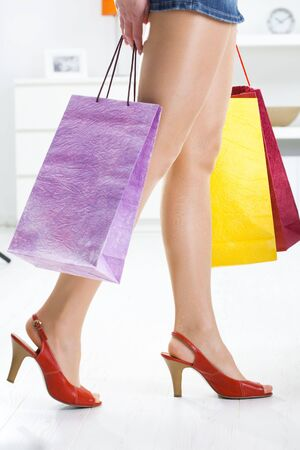 Long female legs in stockings. Hands holding colorful shopping bags. Stock Photo - 5732359
