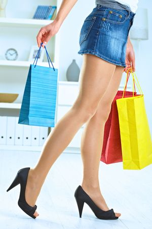 Long female legs in stockings. Hands holding colorful shopping bags. Stock Photo - 5732421