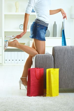 Woman taking off high heel shoe at home, after a day of shopping. photo