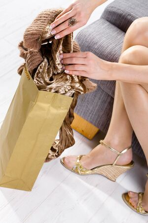 Closeup of female hands packing to shopping bag and legs in stockings and shoes. Stock Photo - 5732427