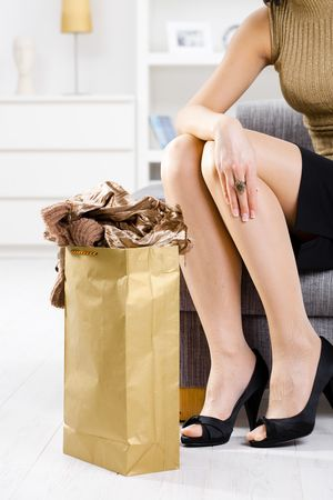 Closeup photo of female hands packing out of shopping bag, legs in stockings and shoes. Stock Photo - 5732430