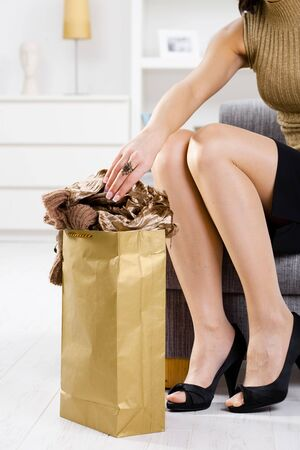 Closeup photo of female hands packing out from shopping bag. Legs in stockings and gold color shoes. Stock Photo - 5732424