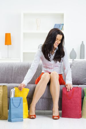 Young woman sitting on couch after day of shopping, packing colorful shopping bags. Stock Photo - 5724675