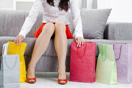 Young woman sitting on couch after day of shopping, packing colorful shopping bags. Stock Photo - 5732432