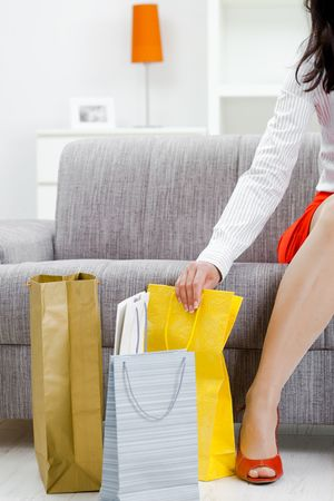 Young woman sitting on couch after day of shopping, surrounded with colorful shopping bags. Stock Photo - 5732500