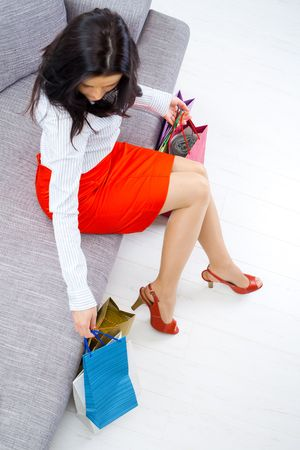 Young woman sitting on couch after day of shopping, packing colorful shopping bags. Overhead shot. Stock Photo - 5724702
