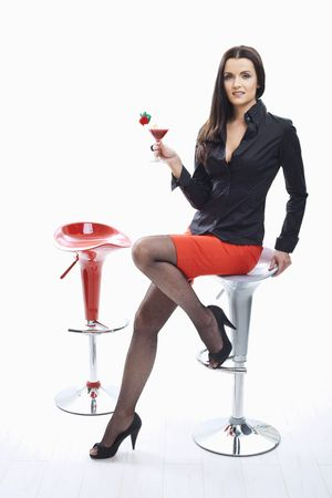 stockings feet: Sexy young woman sitting on bar chair, holding glass of cocktail in hand.