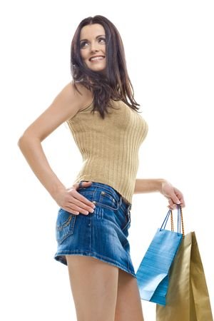 Sexy young woman wearing mini skirt posing with shopping bags. Isolated on whte. photo
