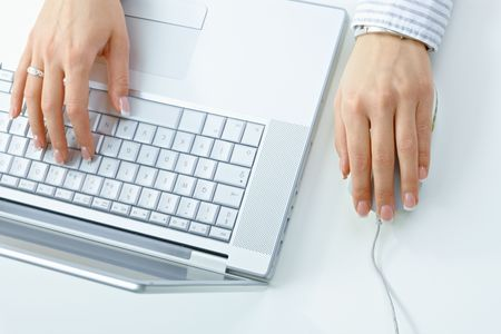Closeup picture of female hand typing on computer keyboard, using mouse. photo