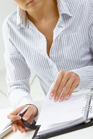 Woman turning a page of personal organizer, focus on hands. photo