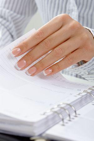 Detalle de mano femenina, pasando de una p�gina de organizador personal. Foto de archivo - 5732406