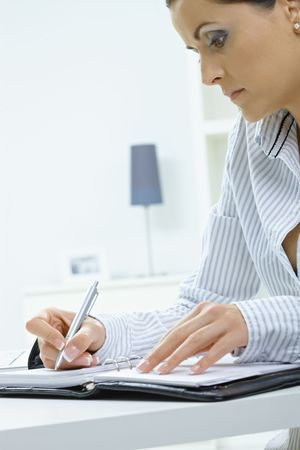 Young woman sitting at desk, writing notes into personal organizer. photo