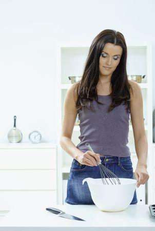 Mujer joven de pie en la mesa de la cocina, batiendo los huevos en un bol, sonriendo. Foto de archivo - 5724575