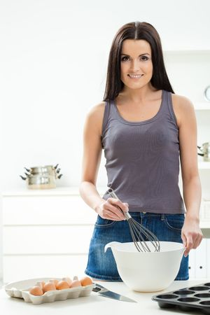 Young woman standing at kitchen table, whisking eggs in a bowl, smiling. Stock Photo - 5724673