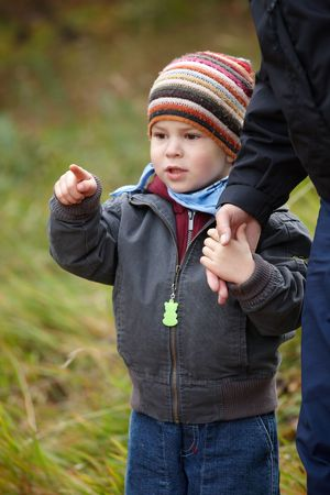 3 persons only: Kid in coat and cap walking hand in hand outdoor in autumn forest.