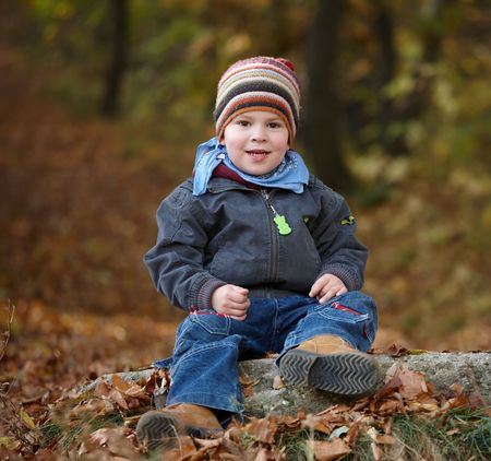 Happy kid in coat and cap playing outdoor in autumn forest, smiling. photo