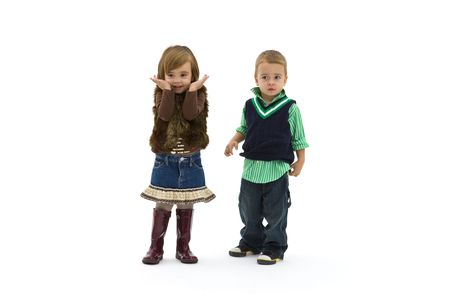 Preschool boy and girl wearing fashionable clothes, looks surprised. photo