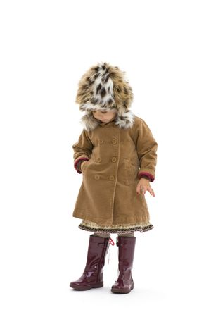 Preschool girl wearing winter clothing. Isolated on white background. photo