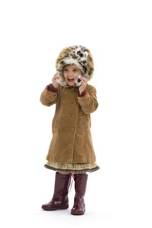 Happy young girl wearing fur hat, brown coat and purple boots. Isolated on white background. photo